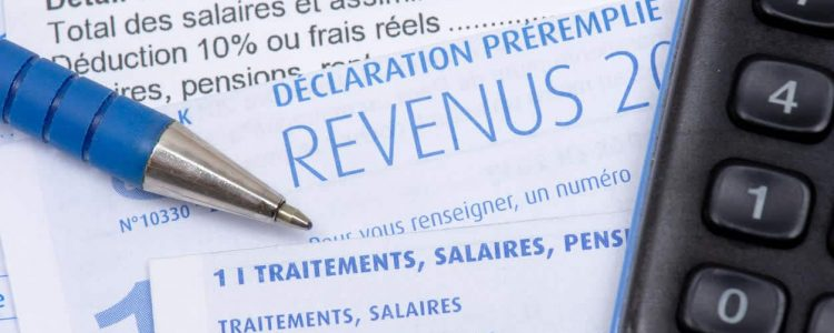 French pre-filled income tax return with the page about income from salaries, treatments, pensions and annuities, along with a pen and a calculator